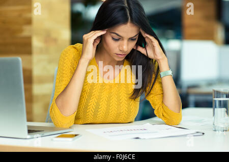 Portrait of a young casual businesswoman reading documents in office - Stock Photo