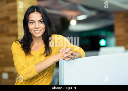Portrait of a happy beautiful businesswoman standing in office and looking at camera - Stock Photo