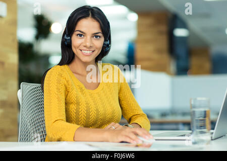 Portrait of a cheerful businesswoman in headphones sitting at her workplace in office and looking at camera - Stock Photo