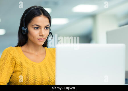 Portrait of a young businesswoman in headphones using laptop in office - Stock Photo