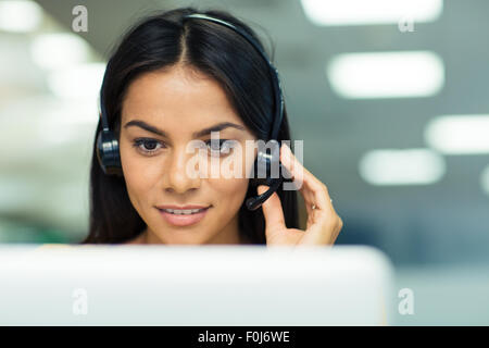 Happy businesswoman working on laptop with headphones in office - Stock Photo