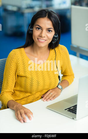 Cheerful businesswoman in sweater sitting at her workplace with headphones in office and looking at camera - Stock Photo
