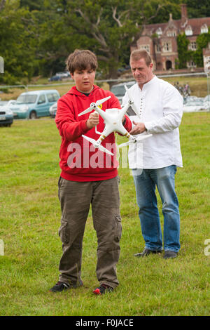 Young man operating Phantom drone with camera attached at the New Forest Fairy Festival, Burley, Hampshire, UK in - Stock Photo