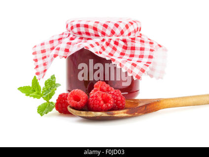 raspberries on wooden kitchen spoon in front of marmalade jar isolated on white background - Stock Photo