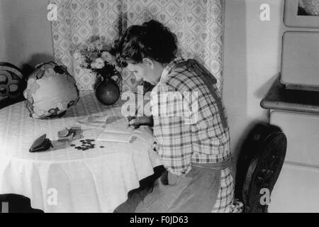 household, woman sitting at kitchen table writing into housekeeping book, 1940s, Additional-Rights-Clearences-NA - Stock Photo
