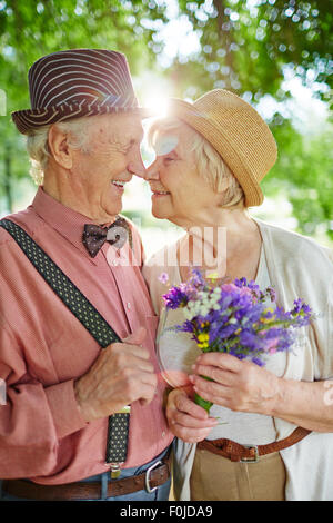 Amorous seniors touching by their noses in natural environment - Stock Photo