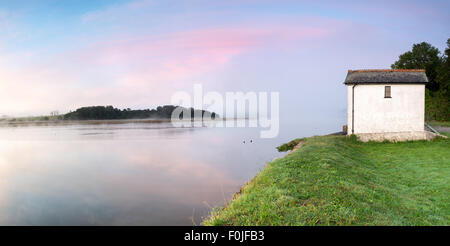 A white house on the side of the river Tamar in Cornwall, on a misty summer morning at Halton Quay - Stock Photo