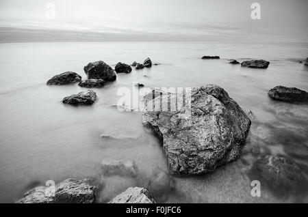 black and white photo of stones on the beach. rocks on the coast - Stock Photo