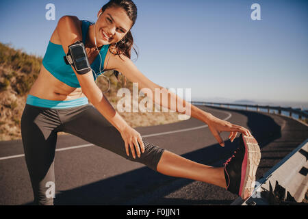 Female athlete stretching her legs outdoor before running. Fit young woman warming up for a run on country road. - Stock Photo