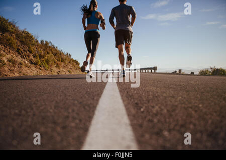Rear view of two young people training together on road. Man and woman on morning run on summer day. Low angle shot - Stock Photo
