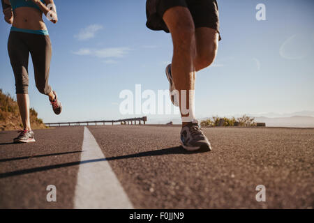 Cropped shot of a young athletes running outdoors. Runners running on a country road on summer morning. Man and - Stock Photo