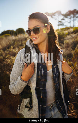 Outdoor shot of happy young woman hiking on a sunny day. Caucasian female hiker wearing sunglasses carrying a backpack - Stock Photo