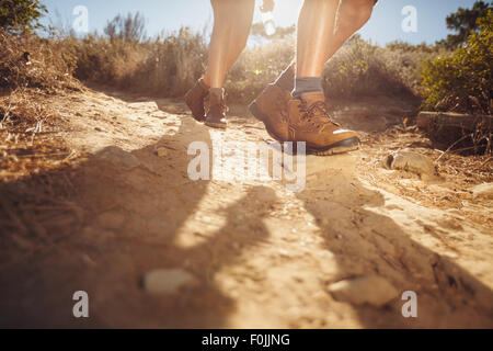 Hiking shoes in action on a country trail path. Close-up of male hikers shoes on dirt trail. Young people hiking - Stock Photo