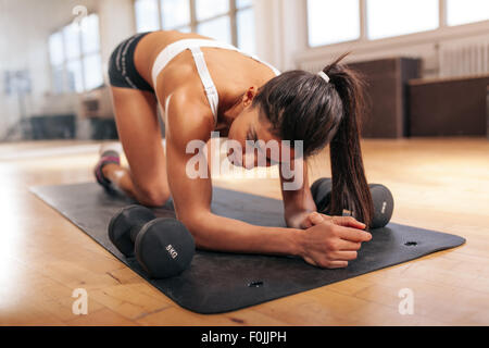 Young woman relaxing after doing pushups, woman exercising on fitness mat with dumbbells in gym. - Stock Photo