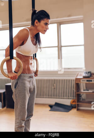 Woman in sportswear working out in a gym doing exercises with gymnastic rings. Tough female athlete doing intense - Stock Photo