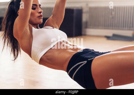 Cropped image of fit young woman exercising at gym. Muscular woman going pull-ups with gymnastic rings. - Stock Photo