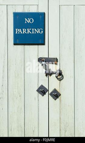 No Parking sign on wooden door, with lock - Stock Photo