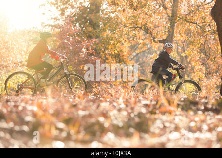 Boy and girl riding bikes in autumn leaves
