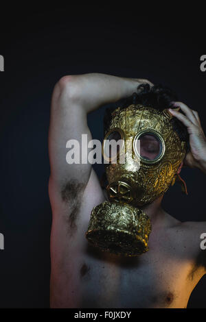 depression and danger man with golden gas mask - Stock Photo