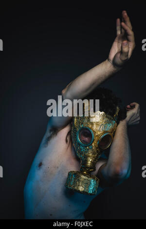 pollution, depression and danger man with golden gas mask - Stock Photo
