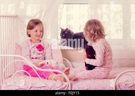 Cute funny little girls (sisters) play in bed, on the window sits a cat. Selective focus. - Stock Photo