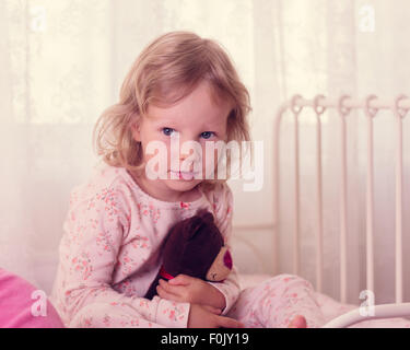 Portrait of a funny little girl in bed with toy. Selective focus. - Stock Photo
