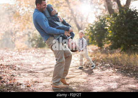 Playful father lifting son upside-down on path in woods - Stock Photo