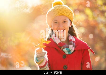 Portrait smiling girl holding golden autumn leaf - Stock Photo