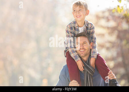 Smiling father carrying son on shoulders outdoors - Stock Photo