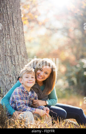 Portrait smiling mother and son at tree trunk in autumn woods - Stock Photo
