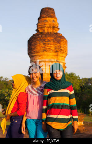 Sumatran girls posing at Muara Takus temple in Riau, Indonesia. - Stock Photo