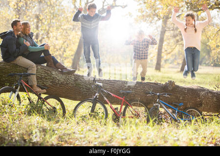 Family playing on fallen log with bicycles in woods - Stock Photo