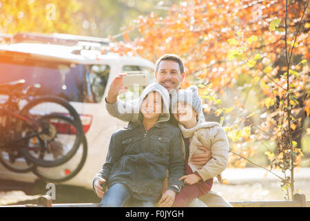 Father and sons taking selfie in autumn park - Stock Photo