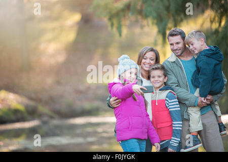 Family taking selfie with camera phone in woods - Stock Photo