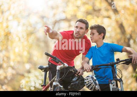 Father pointing and explaining to son on mountain bikes - Stock Photo