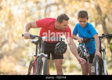 Father and son examining wheel on mountain bike - Stock Photo