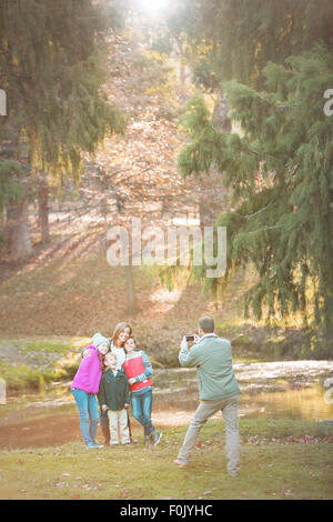 Father photographing family with camera phone in park - Stock Photo