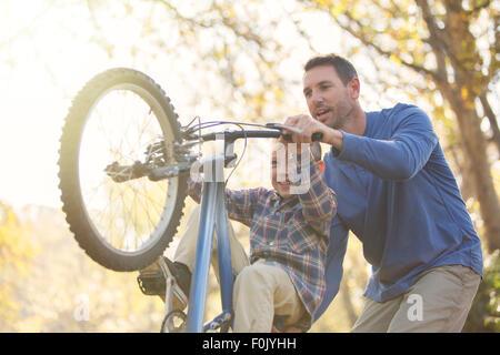 Father teaching son wheelie on bicycle - Stock Photo