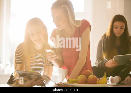 Teenage girls using cell phone and digital tablets - Stock Photo