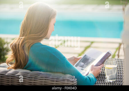 Brunette woman reading magazine at luxury poolside - Stock Photo