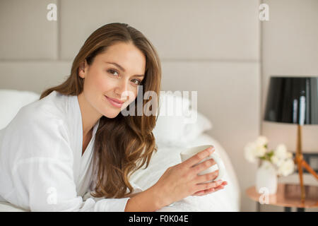 Portrait smiling woman in bathrobe drinking coffee on bed - Stock Photo