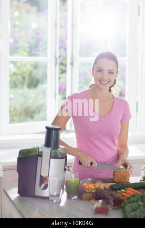 Portrait smiling woman slicing pineapple for juice Stock Photo