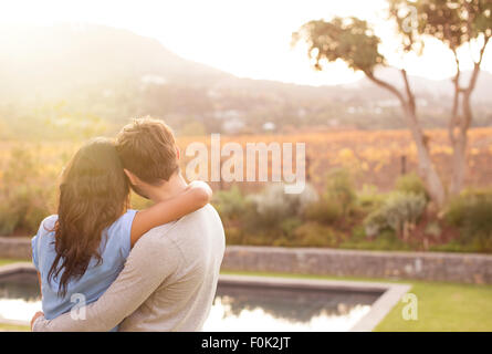 Couple hugging and looking at mountain view poolside - Stock Photo