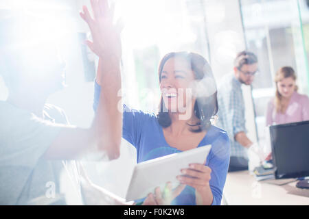 Creative business people high fiving with digital tablet - Stock Photo