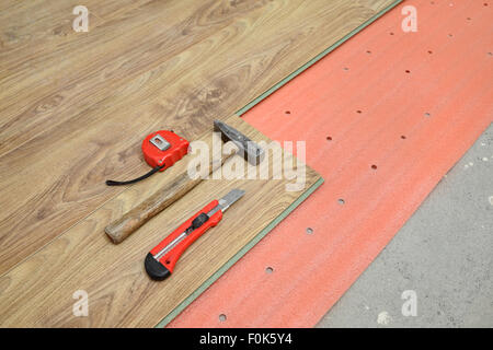 Flooring of room, laminate, foam and tools, hammer, meter, cutter - Stock Photo