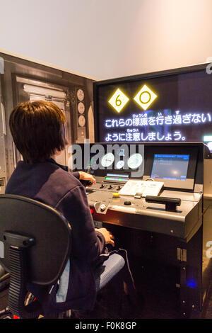Japan, Nagoya, Railway park. Shinkansen Museum. Japanese-English boy sitting at train driving simulator - Stock Photo