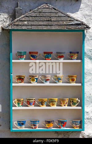 Vertical view of decorated mugs for sale outside a gift shop in Mousehole, Cornwall. - Stock Photo