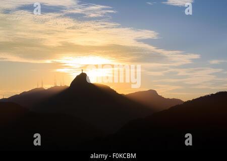 Sun light behind Mountain Corcovado Christ the Redeemer, sunset, Rio de Janeiro, Brazil - Stock Photo