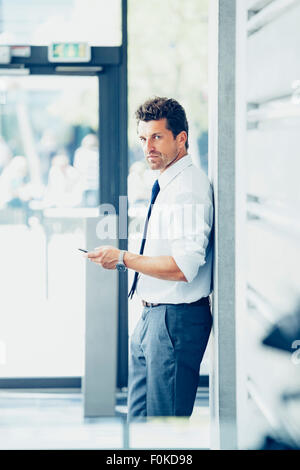 Businessman leaning against a wall holding cell phone - Stock Photo
