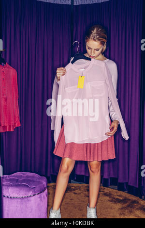 Young woman in fitting room with a blouse - Stock Photo